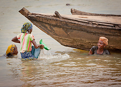 © Licensed to London News Pictures. 05/07/2013. Koulikoro,  Mali.  From left to right - Fatumata (11), Mamouna (12) and Balas (13) will spend 8 hours a day dredging sand which has been dropped by the workers.  The sand is transported to the shore which is then delivered across Mali for use within the construction industry.   Photo credit: Alison Baskerville/LNP