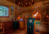 Interior view of a small Orthodox chapel in a Sitka spruce forest near Kodiak, Alaska. Beach shells on top of the chandelier hold hand-dipped beeswax candles.