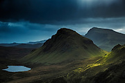 Light hits the dark slopes of the Quirang Mountains on the Isle of Ksye, Scotland