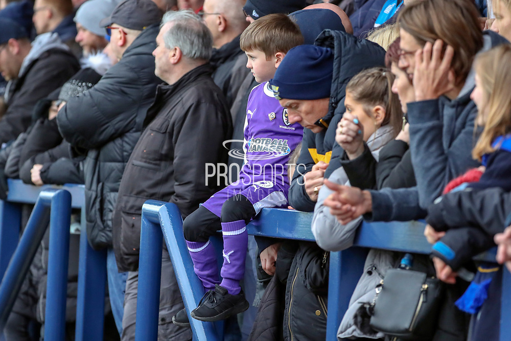 Young AFC Wimbledon fan in goalkeeper kit watching the game during the EFL Sky Bet League 1 match between AFC Wimbledon and Accrington Stanley at the Cherry Red Records Stadium, Kingston, England on 6 April 2019.