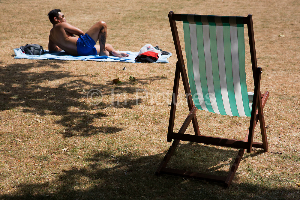 Summertime in London, England, UK. With the grass scorched to brown from the sun a man sunbathes beside a deck chair in St James's Park.