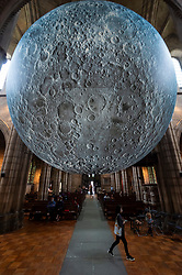 © Licensed to London News Pictures. 19/08/2021. LONDON, UK.  Visitors view Luke Jerram 's Museum of the Moon, a 7m diameter artwork featuring detailed NASA imagery of the lunar surface.  At an approximate 1:500,000 scale, each centimetre of the internally lit sphere represents 5km of the moon's surface. The touring artwork is on display until 30 August at St John the Baptist Church near Shepherd's Bush and forms part of this year's Kensington and Chelsea Festival.  Photo credit: Stephen Chung/LNP