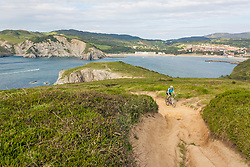 Mountain biker riding uphill by the sea