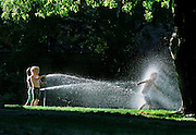 Children play near their home and enjoy the heat of the summer with a cool down with some hoses in Sacramento.