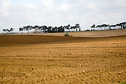 Tractor ploughing land across a shallow valley in Sandlings landscape, Shottisham, Suffolk, England