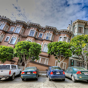 Sloping street with parked cars and illusion of tilted building near downtown San Francisco, CA.
