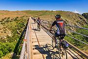 Cyclists crossing a tressel bridge on the Otago Central Rail Trail, Otago, South Island, New Zealand