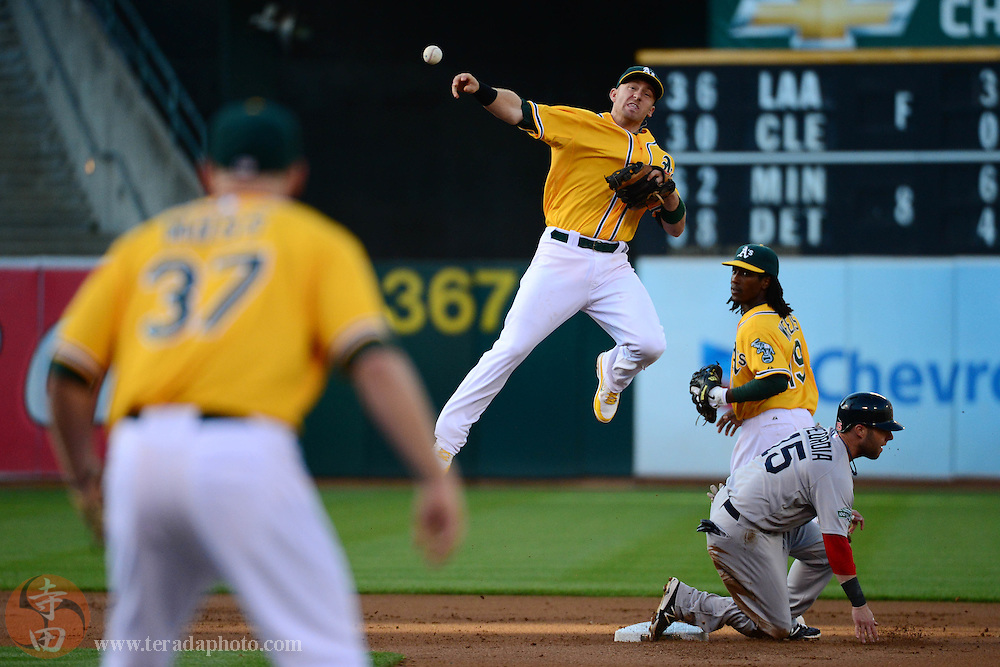 July 2, 2012; Oakland, CA, USA; Oakland Athletics shortstop Cliff Pennington (third from right) completes a double play as Boston Red Sox second baseman Dustin Pedroia (15) slides into second base during the first inning at O.co Coliseum. Pictured: Athletics first baseman Brandon Moss (37) and second baseman Jemile Weeks (far right).