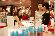 Young Shanghainese women talk while shopping for cosmetics at Parksons, one of Shanghai's best known department stores. This store caters for Western tastes in anything from clothes, to cosmetics, food or electric goods. In such a westernised city, where years ago fashion and modernity did not exist, these places are a Mecca for the young, sometimes affluent youth. Cosmetics are comparatively expensive in Shanghai as in the west, despite the average salary being many times lower. Yet, there is a massive hunger for western goods of all kinds.