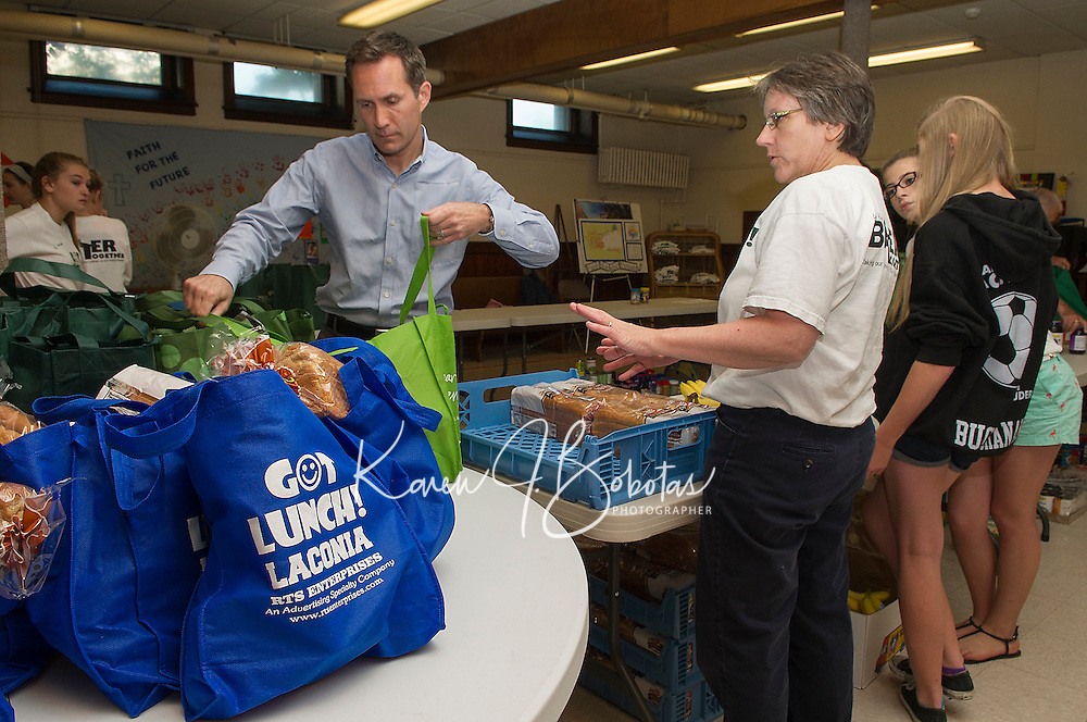 """Mayor Michael Seymour and Diane Pinkham pack up """"Got Lunch"""" bags for the first week's deliveries Wednesday morning in the Congregational Church.  (Karen Bobotas/for the Laconia Daily Sun)"""