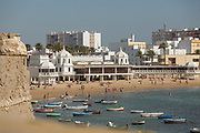 View of beach with tourists and boats on sea, Cadiz, Andalusia, Spain