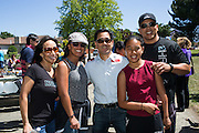 Nob Hill Foods assistant manager Patrick Koda takes a photo with customers during a Nob Hill Foods farewell BBQ at Strickroth Park in Milpitas, California, on May 15, 2016. (Stan Olszewski/SOSKIphoto)