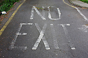 The word NO EXIT fading on a south London housing estate road surface.