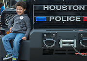 A student sits on a Houston Police Department SWAT vehicle at the When I Grow Up fair, March 8, 2014.