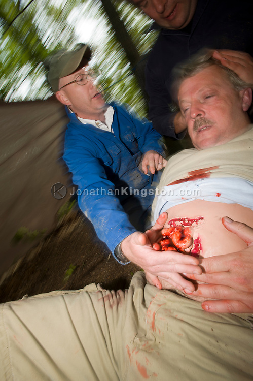 HEFAT course participant Matt Rainey treats Centurion instructor Paul for a stomach wound during a simulated first aid exercise in a refugee camp. Hostile Environments and Emeregency First Aid Training course for journalists deploying to war zones in Strausburg, VA. (Not Released)
