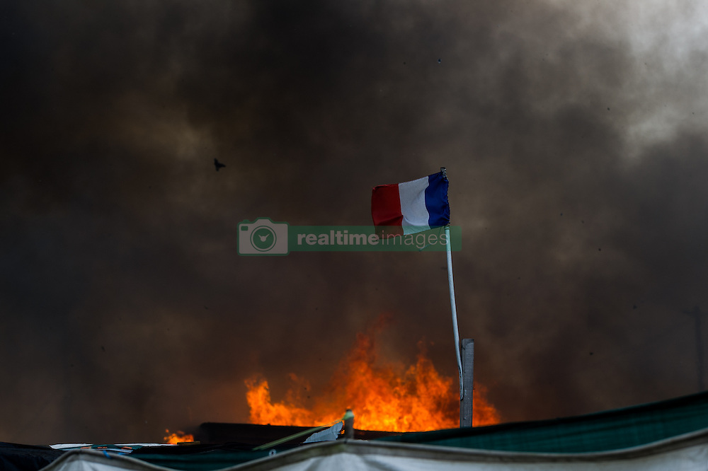October 26, 2016 - Calais, France - A french flag blows in the Calais Jungle in front of the flames of a burning hut, on October 26, 2016. Huge fires destroyed a mayor part of the refugee camp today. (Credit Image: © Markus Heine/NurPhoto via ZUMA Press)