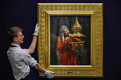 "© Licensed to London News Pictures. 11/10/2019. LONDON, UK. A technician presents ""Lighting the Lamp"", by Antonio Fabrés Y Costa, (Est GBP100-150k).  Preview of works from the Najd Collection of orientalist paintings at Sotheby's in New Bond Street, which record daily life in the historic Arab, Ottoman and Islamic worlds  All 155 paintings are on public view 11- 15 October, with 40 works to be auctioned on 22 October.  Photo credit: Stephen Chung/LNP"