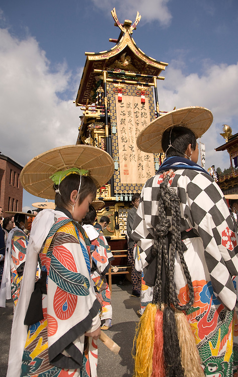 Asia, Japan, Gifu prefecture, Takayama (also known as Hida-Takayama), boys in traditional costumes and elaborate festival float (yatai)  which is pulled through streets in Gonjunko Procession during Sanno Festival of Hie Jinja Shrine, held annually in April.