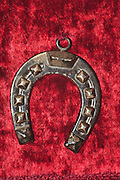decorated silver horseshoe amulet on red velvet background