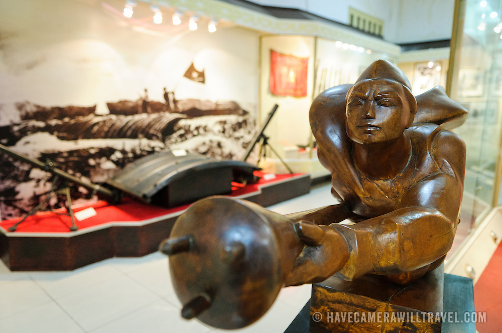 A stylized revolutionary statue at right and an exhibit of light artillery mortars in the background as part of the revolution's military campaigns. The Museum of the Vietnamese Revolution in the Tong Dan area of Hanoi, not far from Hoan Kiem Lake, was established in 1959 and is devoted to the history of the socialist revolutionary movement in Vietnam.