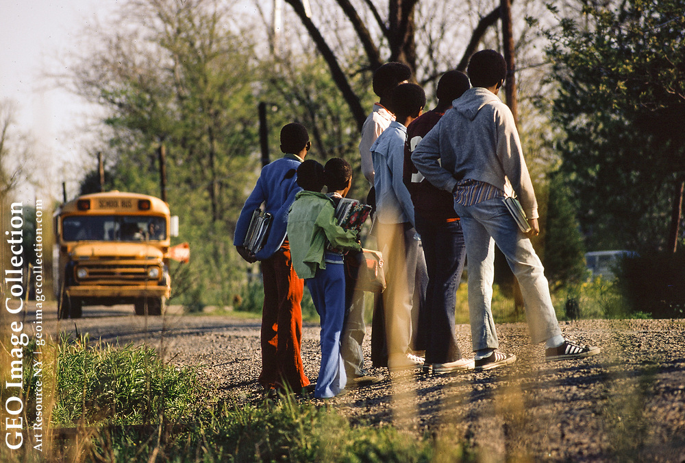 Schoolchildren wait for bus in Beulah, MS, a Mississippi Delta town that grew as a result of exodus from plantations. Traditionally Beulah was a cotton growing plantation, more recently replaced by soybeans. Much of the African-American population migrated to northern cities in 20th century .