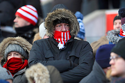 A Stoke City fan keeps warm ahead of the Premier League match at the bet365 Stadium, Stoke.