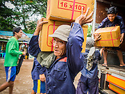 """10 JUNE 2014 - YANGON, MYANMAR:   Porters carry boxes candles to a waiting river boat on the banana jetty. The """"banana jetty"""" is on the Yangon River north of central Yangon on Strand Road. Bananas, coconuts and other fruit are brought in here from upcountry, sold and reshipped to other parts of Myanmar (Burma). All of the labor here is done by hand. Porters carry the produce to the jetty and porters load the boats before they steam upriver.   PHOTO BY JACK KURTZ"""