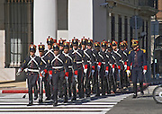The change of the honour guard on the Plaza Independencia Independence Square. The honour guard guards the mausoleum of General Artigas. Men in old style uniforms marching across a pedestrian crossing supervised by an officer. parade Montevideo, Uruguay, South America