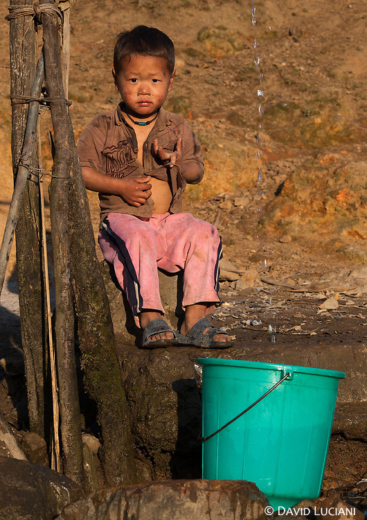 A boy posing near a water well in Pangi village.