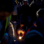 CARRICKMINES, DUBLIN, IRELAND - OCTOBER 14, 2015: A child lites a candle as hundreds of people gathered at the scene of a fatal fire in Carrickmines, in sout Dublin, for a candlelight vigil. Candles were lit and placed alongside the floral tributes at the entrance to the halting site where the ten people died. CREDIT: Paulo Nunes dos Santos for The New York Times