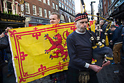 Bagpiper plays for Scotland fans in joyous mood drinking and singing together in Covent Garden ahead of their football match, England vs Scotland, World Cup Qualifiers Group stage on 11th November 2016 in London, United Kingdom. The Home International rivalry between their respective national teams is the oldest international fixture in the world, first played in 1872.