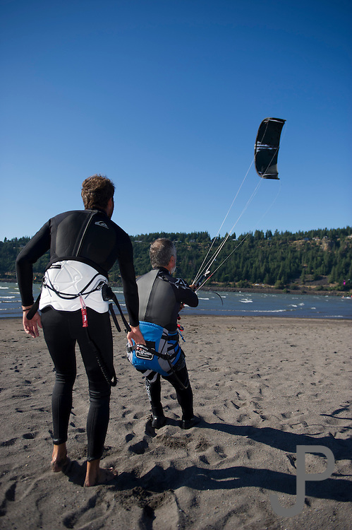 Alfonso is intimidated by the high winds at Hood River.  He has only been kiteboarding three years.  Fernando helps hold Alfonso against the wind.