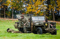 Pickering War Weekend 2009 A member of the Northern World War Two Associations 101st Airborne Living History Group returns fire from a Willys Jeep after being ambushed by enemy troops. Large large battle reenactment <br /> Copyright Paul David Drabble