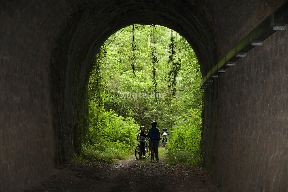 parent with children at the end of an old railroad tunnel