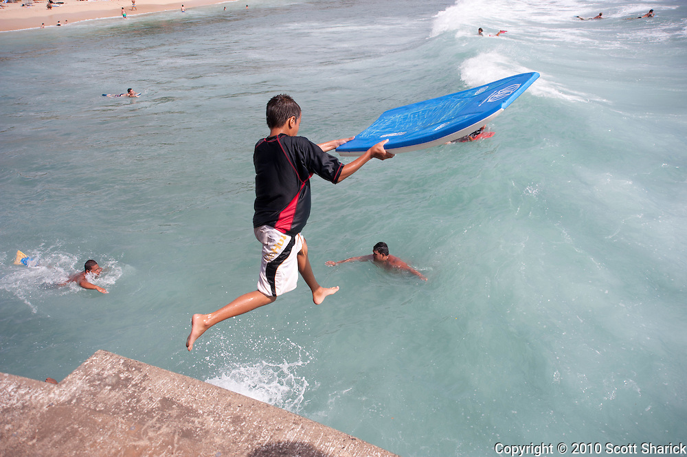 A young boy with a boogie board jumps off a pier into the ocean in Waikiki.