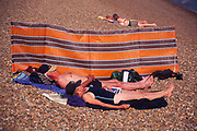 AJDNC9 Elderly couple sunbathing by windbreak Shingle Street Suffolk England