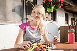 Young woman eating salad at alpine cabin, Kampenwand, Bavaria, Germany