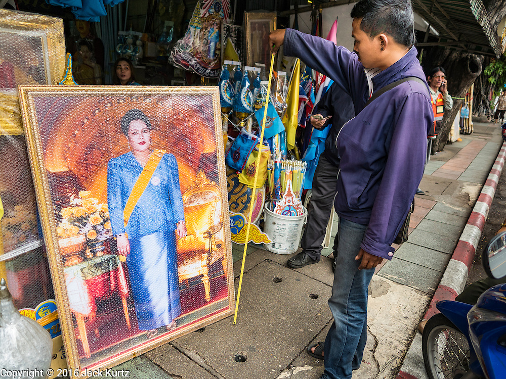 10 AUGUST 2016 - BANGKOK, THAILAND: A Thai man measures a portrait of Queen Sirikit he bought to display on her birthday. Thais are preparing for the Queen's birthday. Queen Sirikit of Thailand, was born Mom Rajawongse Sirikit Kitiyakara on 12 August 1932. She married  Bhumibol Adulyadej, King of Thailand (Rama IX) in 1950. He is the longest serving monarch in the world and she is longest serving consort of a monarch. Her birthday, like the King's Birthday (which falls on Dec. 5),  is a national holiday in Thailand. Her birthday, August 12, is also celebrated as Mothers' Day in Thailand. Thais hang portraits of Queen Sirikit in their homes and fly her royal flag on her birthday.        PHOTO BY JACK KURTZ