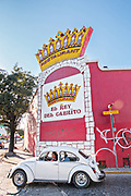 A old Volkswagen Beetle drives past the brightly painted El Rey del Cabrito restaurant in the Barrio Antiguo or Spanish Quarter neighborhood adjacent to the Macroplaza Grand Plaza in Monterrey, Nuevo Leon, Mexico.