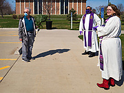 "05 APRIL 2020 - DES MOINES, IOWA:  Rev. BONNIE PARKER, right, and Rev. RUSSELL LACKEY, center, talk to a parishioner after a drive through Palm Sunday service sponsored by Luther Memorial Church on the campus of Grand View University in Des Moines. About 150 people attended the service. They remained in their cars while the ministers read a short passage from the Bible, handed out palms and blessed them. On Sunday, 05 April, Iowa reported 868 confirmed cases of the Novel Coronavirus (SARS-CoV-2) and COVID-19. There have been 22 deaths attributed to COVID-19 in Iowa. Restaurants, bars, movie theaters, places that draw crowds are closed until 30 April. The Governor has not ordered ""shelter in place"" but several Mayors, including the Mayor of Des Moines, have asked residents to stay in their homes for all but essential needs. People are being encouraged to practice ""social distancing"" and many businesses are requiring or encouraging employees to telecommute.        PHOTO BY JACK KURTZ"