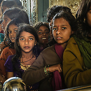 This group of young teenagers must be from the same class and are waitng in line to enter a crowded temple.