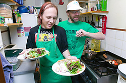 Two chefs working in a cramped kitchen of a vegetarian café at the Sumac Centre; Nottingham; the centre provides resources and a meeting place for local groups and individuals campaigning for human and animal rights; the environment; peace and cooperation worldwide,