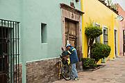 An elderly Mexican man sharpening knives along a colorful alley in the old colonial section of Santiago de Queretaro, Queretaro State, Mexico.