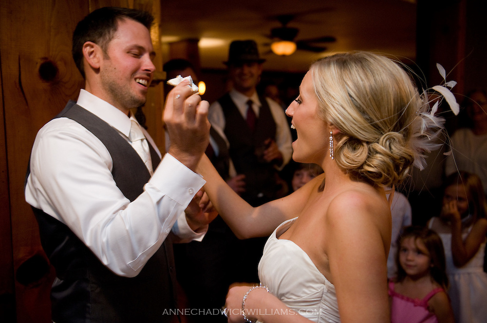 Bride and groom feed each other cake at their wedding reception at Forest House Lodge in Foresthill, CA.