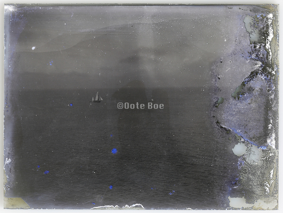 seascape with sailing boat on a fading vintage glass plate