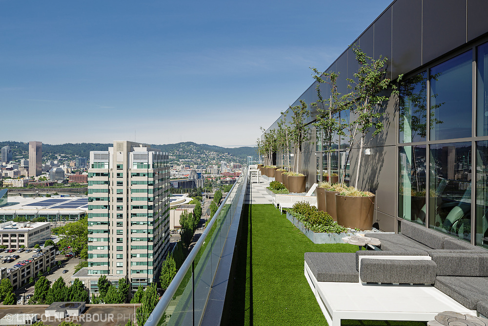 A nice view of Portland from a terrace at the top of a high rise apartment building. Nice furniture, astroturf, and medium sized trees decorate the terrace.
