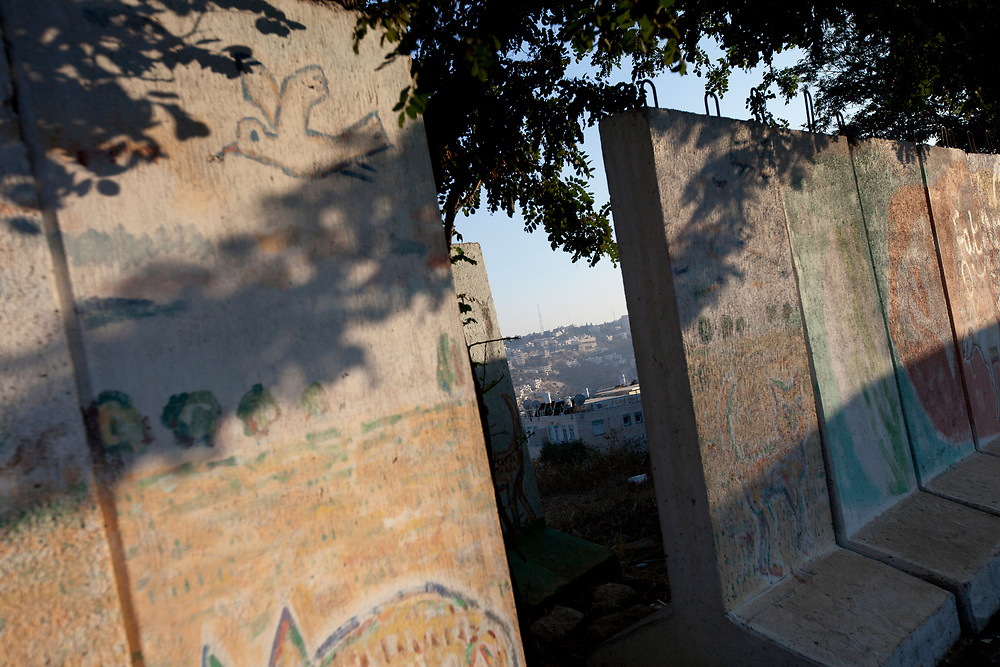 The Palestinian village of Beit Jalla is seen through an opening in a section of the Gilo protective wall in Jerusalem, on August 12, 2010. On Sunday, August 15, the IDF will begin to dismantle the wall which protected the residents of Gilo neighborhood in Jerusalem, from gunfire and mortar shells. The wall was put up in 2001, during the Second Intifada, when Gilo came under intense near daily attacks from the adjacent Arab village of Beit Jalla, which had been handed over to the Palestinian Authority under Yasser Arafat, as part of the Oslo Accords. The IDF stated that the decision to remove the wall was preceded by a security assessment at Central Command which determined that the move was a safe one.