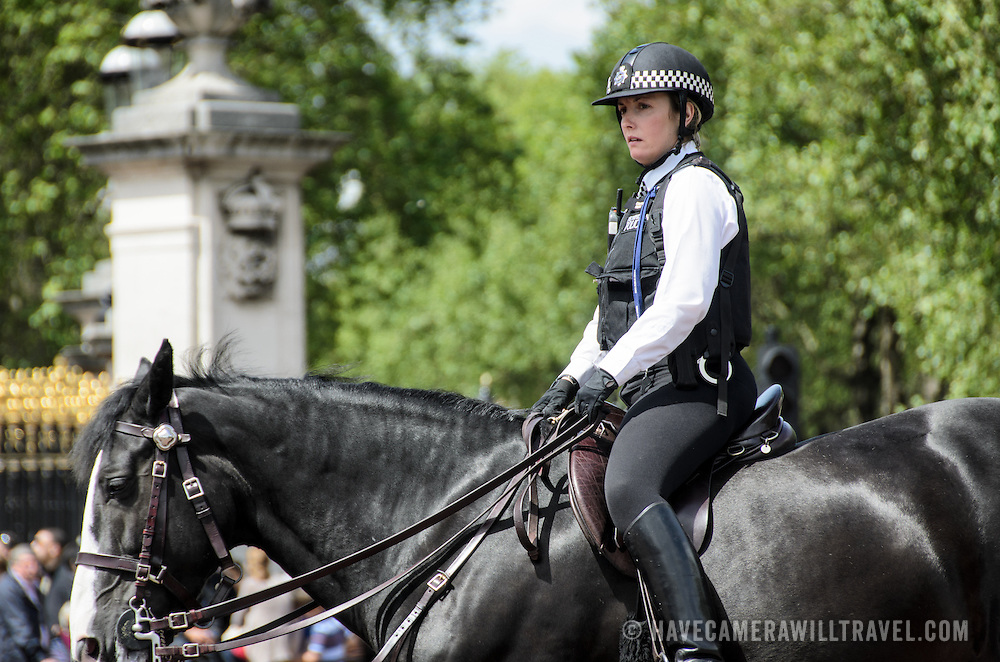 Mount Police Woman Supervising Tourist Crowds 169-110307698x A mounted policewoman from the London Metropolitan Police Service supervises the crowd of tourists at the Changing of the Guard Ceremony in front of Buckingham Palace from atop a black horse.