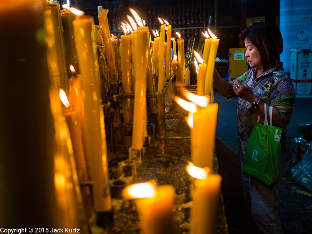 15 OCTOBER 2015 - BANGKOK, THAILAND: A woman prays and lights candles during the Vegetarian Festival at the Joe Sue Kung Shrine in the Talat Noi neighborhood of Bangkok. The Vegetarian Festival is celebrated throughout Thailand. It is the Thai version of the The Nine Emperor Gods Festival, a nine-day Taoist celebration beginning on the eve of 9th lunar month of the Chinese calendar. During a period of nine days, those who are participating in the festival dress all in white and abstain from eating meat, poultry, seafood, and dairy products. Vendors and proprietors of restaurants indicate that vegetarian food is for sale by putting a yellow flag out with Thai characters for meatless written on it in red.    PHOTO BY JACK KURTZ