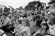 """A crowd of Londoners laugh during an afternoon's Punch and Judy show at The Lambeth Show in Brockwell Park, Herne Hill, England. Children of all ages along with parents grin at the out-of-sight puppet entertainment during this public festival of amusements and stalls in London's inner-city. Only one young girl sits unimpressed at the standard of comedy. She sits with her mother looking serious while the kids nearby roar with laughter - hugely involved with the show. From a personal documentary project entitled """"Next of Kin"""" about the photographer's two children's early years spent in parallel universes. Model released."""